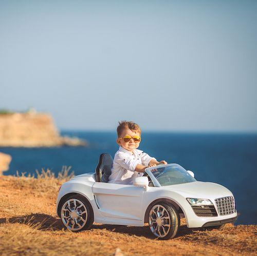 Cooler kleiner Junge sitzt im Spielzeugauto