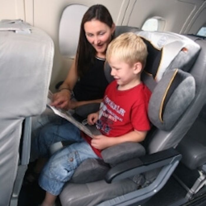 Mutter und Kind mit Kindersitz im Flugzeug